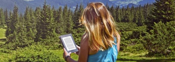 Close-up of woman reading e-book in nature. Girl holding tablet computer screen which is editable isolated on forest background in Dragobrat ,Carpathian mountains