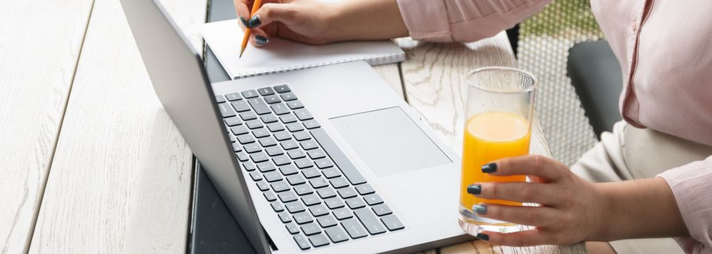 Close up portrait of a young woman working on laptop and writing, holding a glass of orange juice.