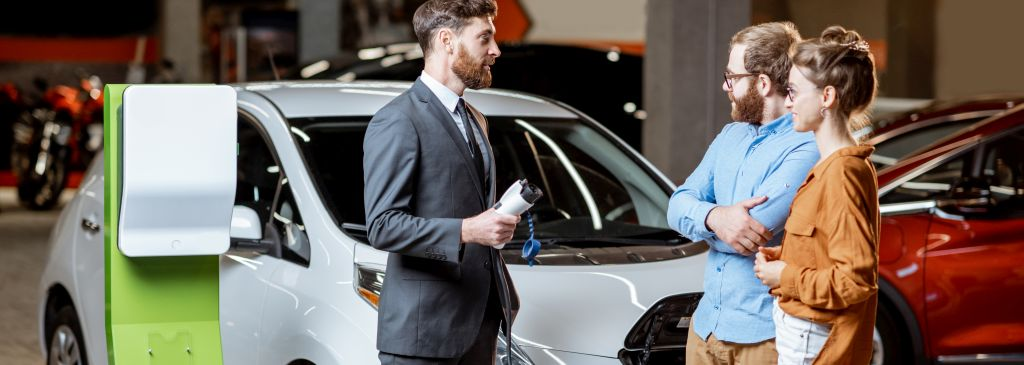 Sales manager selling electric car to a young couple