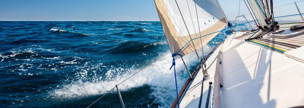 Sailing boat at open sea in sunshine