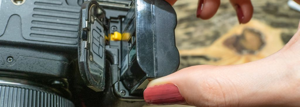 A photographer changes the battery in his SLR camera while shooting in the Studio. focus on the camera battery