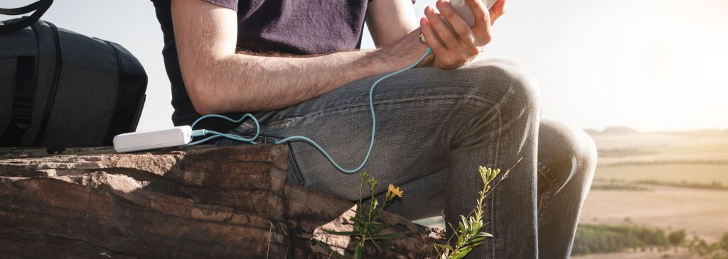 Man on a hike uses smartphone while charging from the power bank on the rock at dawn. Healthy lifestyle and communication.